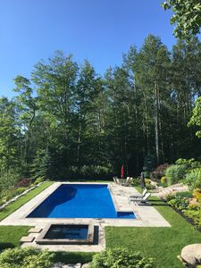50ft pool & hot tub are sunk into the grassy platform against the panoramic view