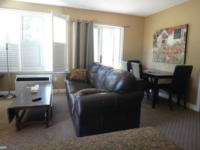 Comfortable Living room includes lots of bright windows with California Shutters