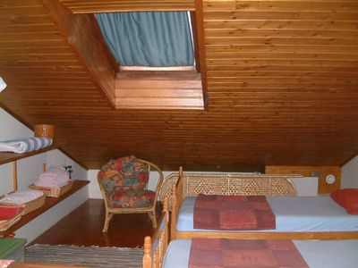 Twin beds on the mezzanine showing wood panelled ceiling