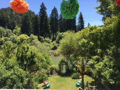 View from the deck of part of the backyard, redwoods, flowers and RIVER!