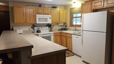 The kitchen has all the essentials, microwave, stove, dishwasher, refrigerator.