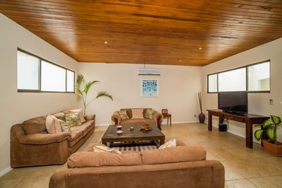Living room with flat screen TV, surround sound, Apple TV and DVD collection