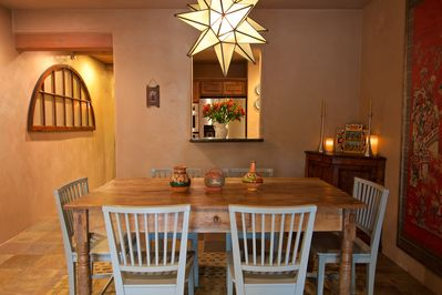 The open living area includes an antique Spanish colonial dining table.