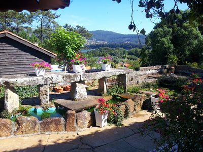 view from covered terrace over fish pond towards the estuary and Portugal