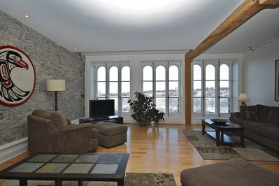 The living room boasting huge windows overlooking the Saint-Lawrence River.
