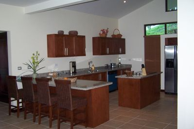 Fully equipped modern kitchen with granite counter tops and stainless appliances