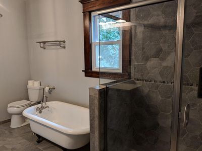 The restored 1800s claw-foot tub and ultra-modern tiled shower downstairs