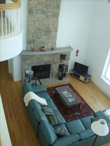 Maine-modern interior with custom fireplace. Upstairs balcony/sunroom visible.