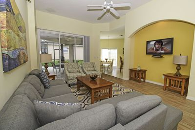 Family seating area showing patio doors to pool and wall mounted flatscreen TV