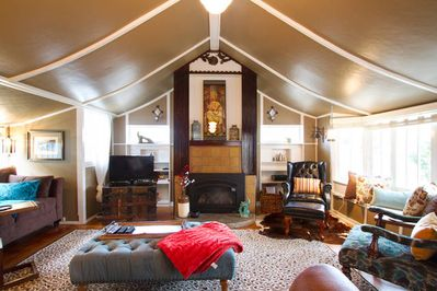 Spacious living room with tented cathedral ceiling and adorned fireplace