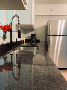 The kitchen has a granite counter top & stainless steel full-size refrigerator.