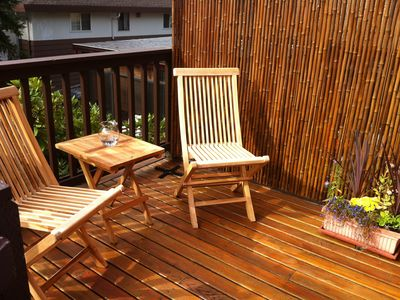 Private deck with bamboo screen, plants and teak bistro set for two.