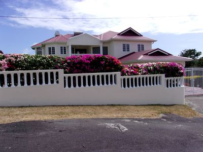 Frontal  view of Rayhope house from with blooming Bougainvillea in foreground