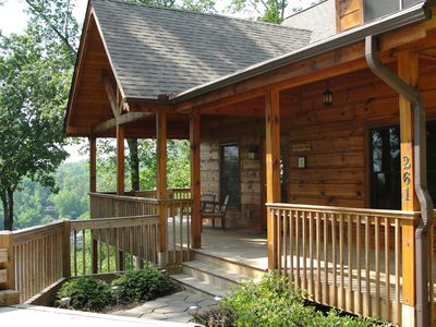 Front view of cabin with covered porch and wrap around deck with lake views!