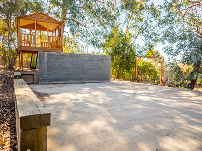Large backyard with half court, cubby house, swing set and trampoline
