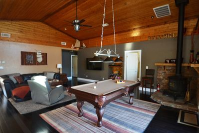 """Open-concept family room adjacent to kitchen with pool table and 63"""" tv."""
