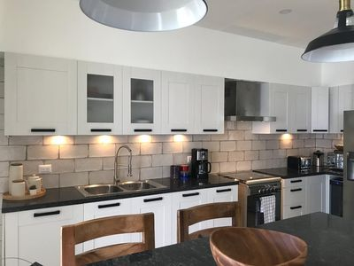 well appointed and lit kitchen with added bartop seating for convenience