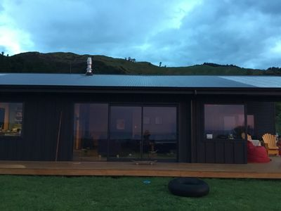 front of house, sliding doors open onto deck which wraps around house
