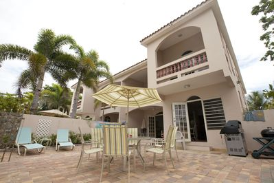 Private patio with tables and chairs and plenty of chaise lounges