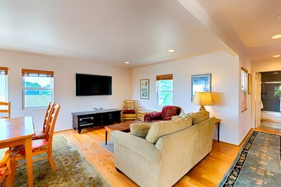 Spacious living room is open with dining area and comfy furnishings and a flat screen TV for your enjoyment.