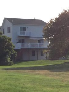 Back of house showing deck with open awning and balcony off master