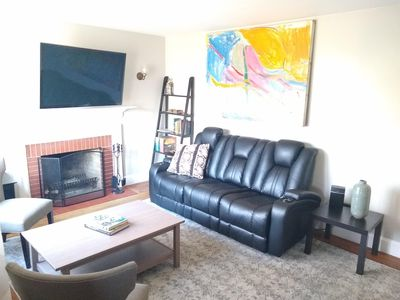 Living room features a 55 inch mounted flatscreen TV and working fireplace.