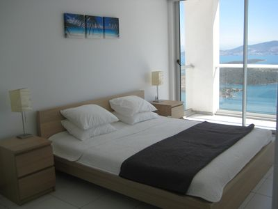 King size bed with floor to ceiling windows and views over the bay