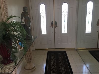 Entry doors with statue, mirrored wall, marble flooring.