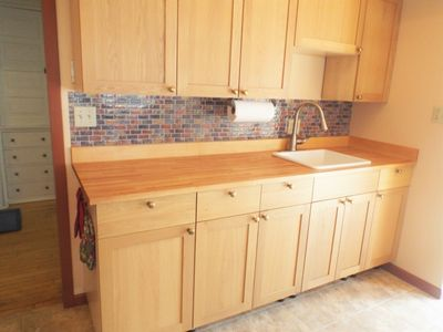 Fully equipped kitchen with  stove, oven, cookware, dishes, cutlery, and more.