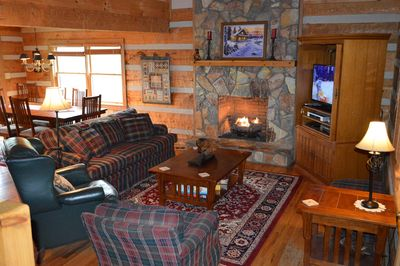 Living room area with gas log stone fireplace with TV