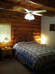 Cozy log bedroom on main with queen bed, french doors and shared bathroom.