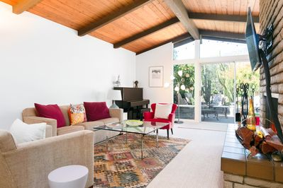 Living Room - Open-beam ceilings soar in the sun-drenched living room, where big windows overlook the fruit grove.