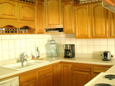 Kitchen with dishwasher, microwave oven, refrigerator, coffee maker, dishes etc.