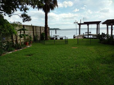 Fenced yard with lake views, concrete table and benches, fishing & jet ski dock.