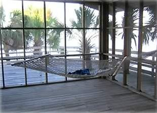 View from inside screened porch, looking east toward deck and the Gulf