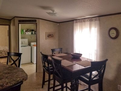 Dining area. Partial view of laundry room with full washer and dryer