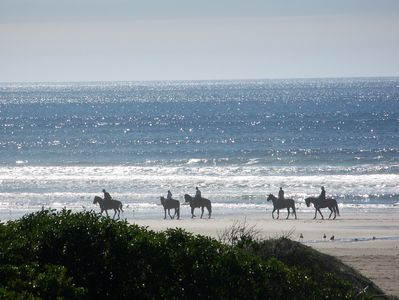 Horseback riders on the beach in front of the house
