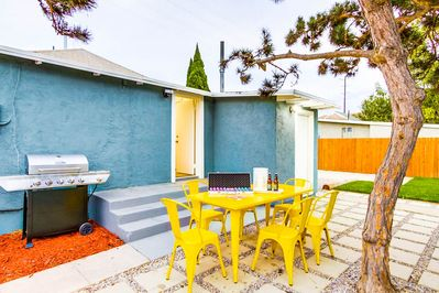 Vibrant backyard with barbecue grill and dining table.