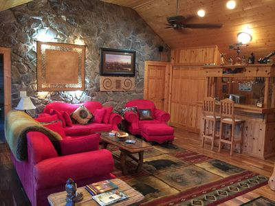 """Living room area with wet bar and 65 """" 4K curve TV"""