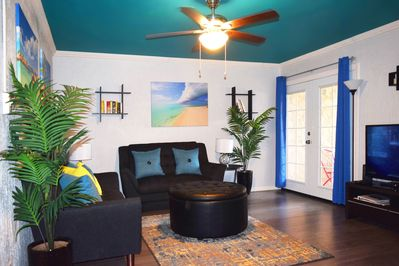 Lounge in the tropical themed living room and a private patio near the pool area