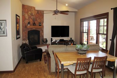 Living room with large flat screen TV and fireplace.