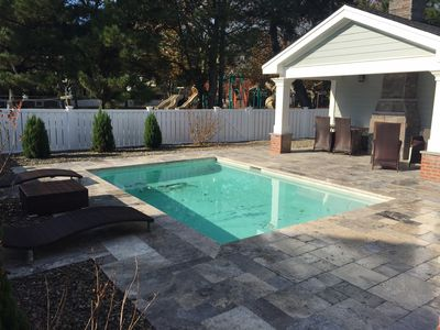 View of pool area, with chaises and view of Chelsea Park accessible from yard