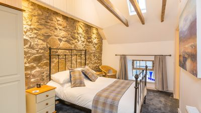 Masterbedroom, original stone wall and timber beams softened with tweeds