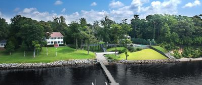 A bridge connects the pool house/deck (right) to the main house (left)