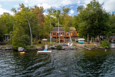 Aerial View of the Lake-house with picnic table, floating dock, & water crafts.