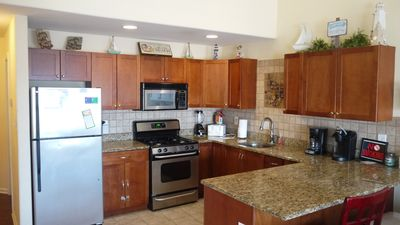 Stainless Kitchen, granite counters, tile floor and decorative art