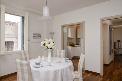 Dining room with separate kitchen in background & canal views through 3 windows