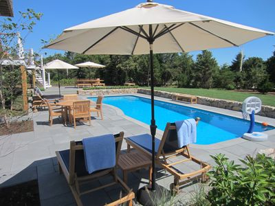 15x38 foot Heated Pool with chaises, tables and umbrellas