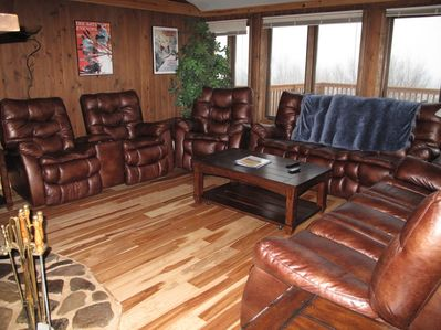 Incredible living room featuring seven reclining seats and new hardwood floors.