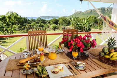 Outdoor dining on a large verandah with a view of Falmouth bay. Seating for 4